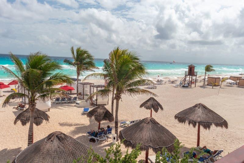 Caraïbisch strand met wit zand, turkooise overzees, palmen, hutten en bewolkte hemel stock fotografie