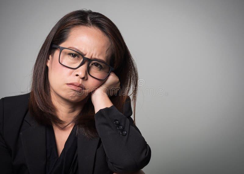 Cara aborrecida asiática da mulher adulta Retrato de mulheres de negócio no bla fotos de stock royalty free