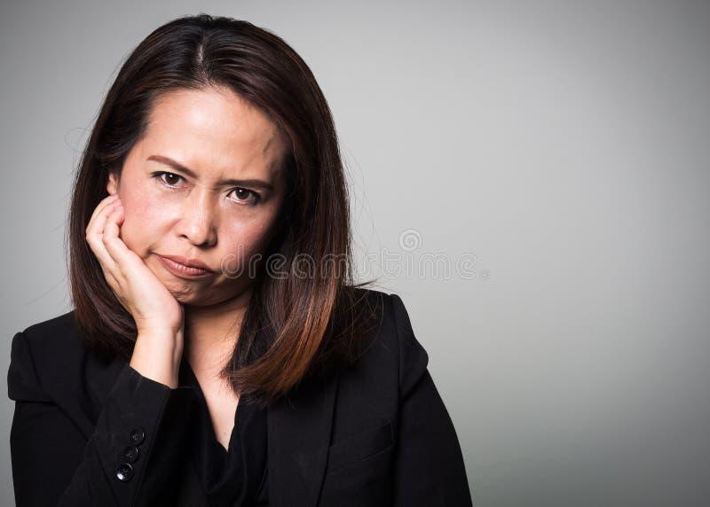 Cara aborrecida asiática da mulher adulta Retrato de mulheres de negócio no bla fotos de stock