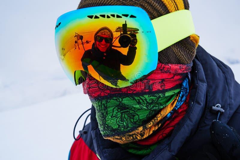 A cara alegre do fotógrafo é refletida no snowboarder da máscara, close up imagem de stock