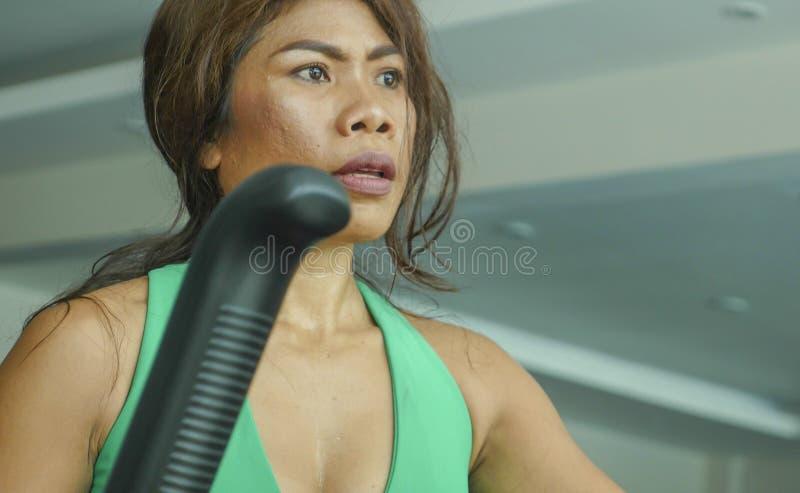 Cara ascendente cercana de la mujer asiática resuelta y enfocada joven en el gimnasio que hace entrenamiento en la máquina elípti imagenes de archivo