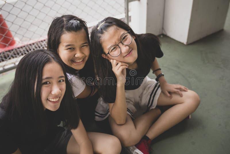 Cara ascendente próxima da felicidade do adolescente asiático que relaxa no lugar da escola fotografia de stock royalty free