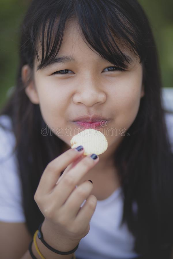 Cara ascendente próxima do adolescente asiático que come o alimento de petisco com cara da felicidade imagem de stock royalty free