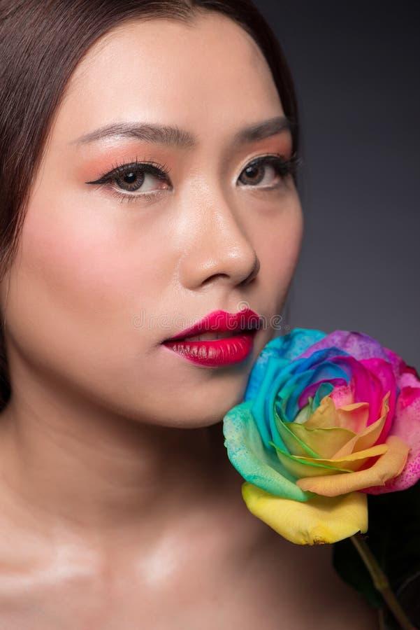 Cara asiática bonita da mulher com composição perfeita com as flores da fotografia de stock