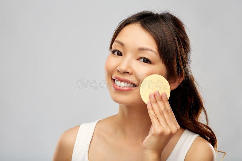 Cara asiática da limpeza da mulher com esponja exfoliating fotografia de stock royalty free