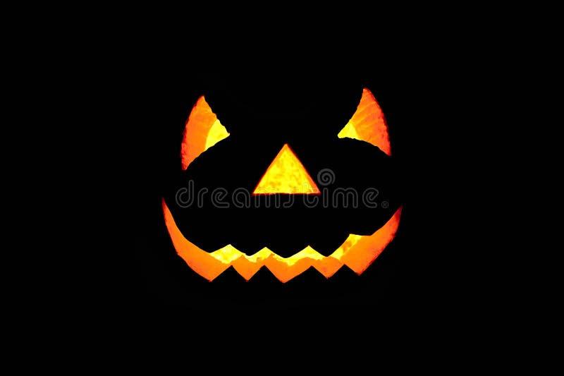 Cara assustador de incandescência feita da abóbora no fundo preto Halloween imagens de stock royalty free