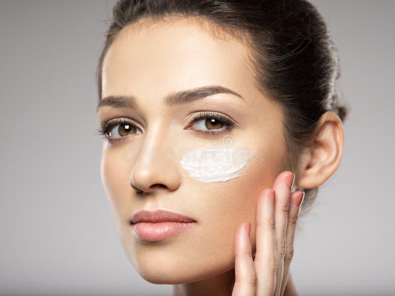 Cara bonita da jovem mulher com creme cosmético na cara imagens de stock