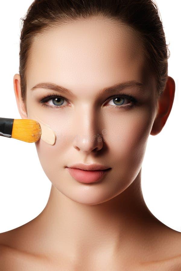 Cara bonita da jovem mulher com fundação cosmética em uma pele foto de stock royalty free