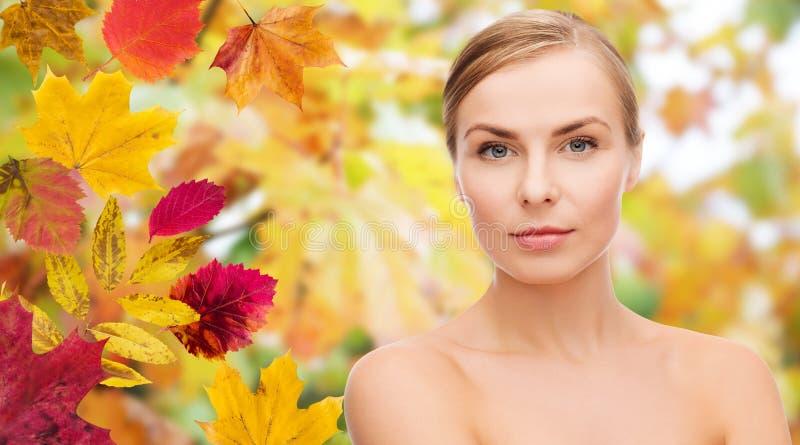 Cara bonita da jovem mulher sobre as folhas de outono imagens de stock royalty free