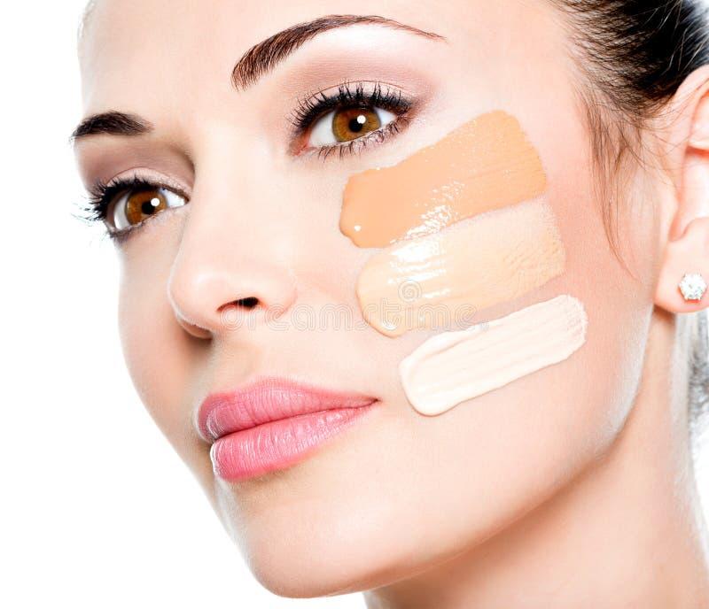 Cara bonita da mulher com fundação cosmética em uma pele fotografia de stock