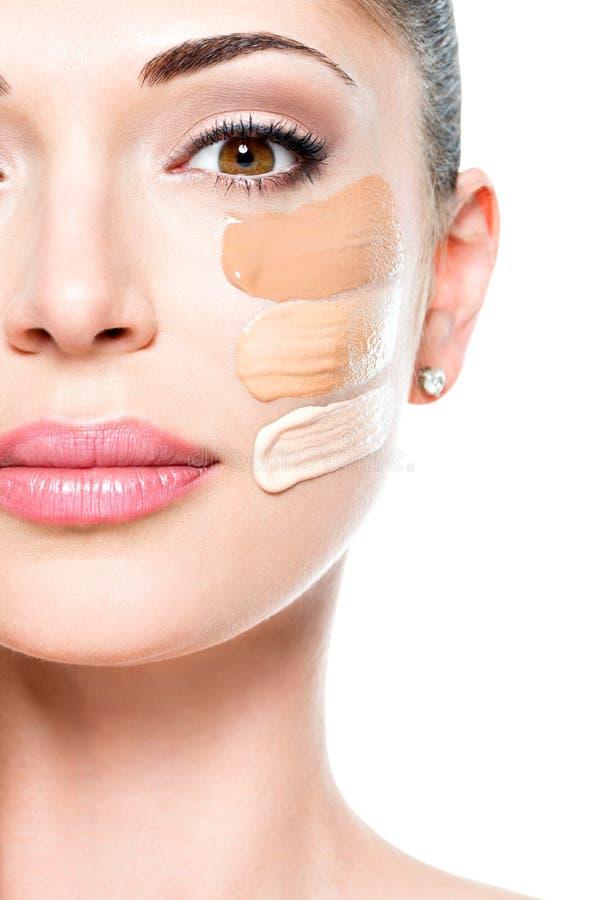 Cara bonita da mulher com fundação cosmética em uma pele imagem de stock royalty free