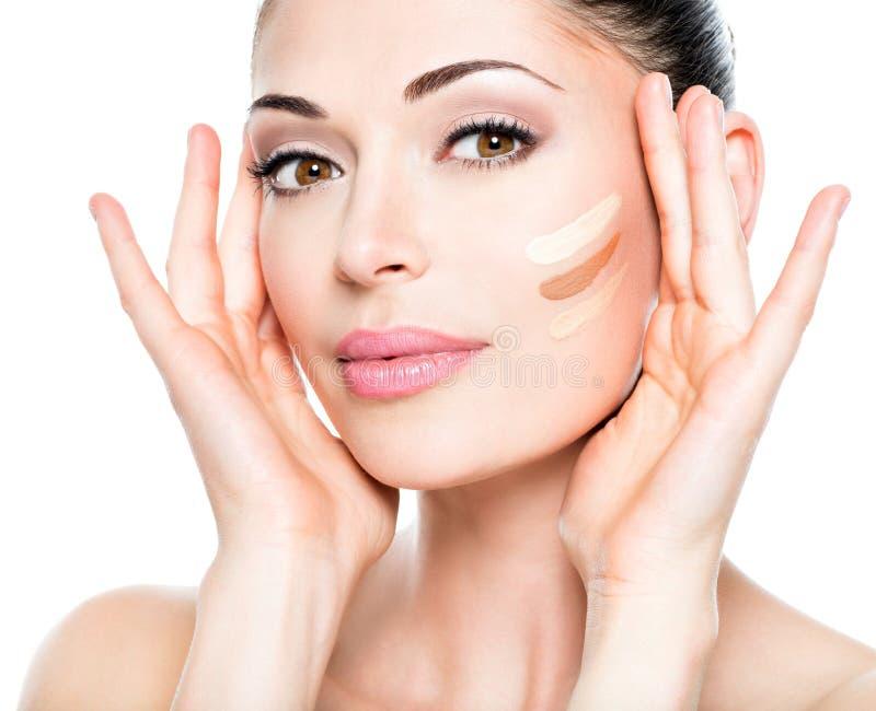 Cara bonita da mulher com fundação cosmética em uma pele foto de stock