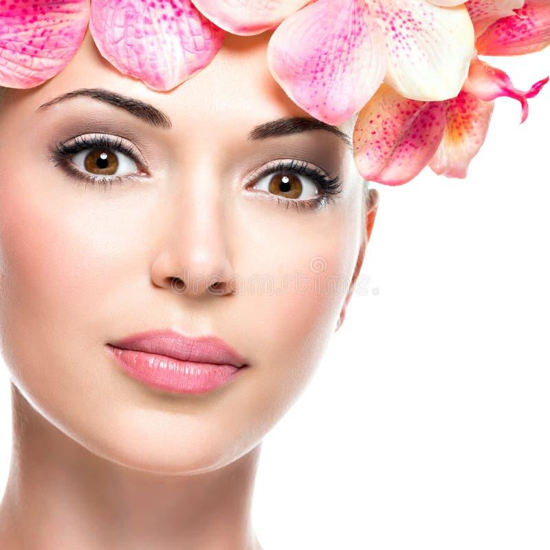 Cara bonita da mulher com pele saudável e as flores cor-de-rosa fotos de stock royalty free