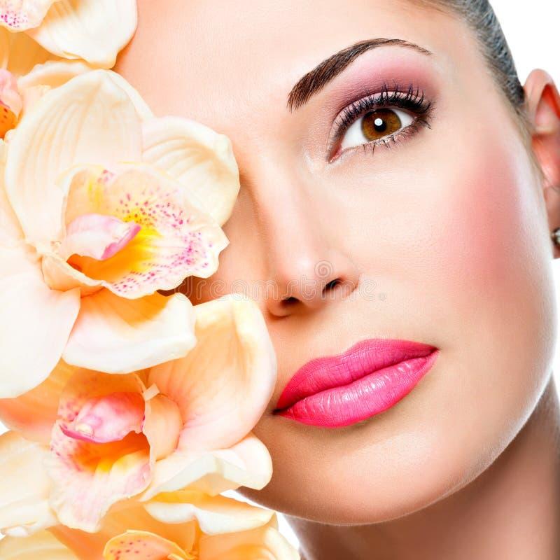 Cara bonita da mulher com pele saudável e as flores cor-de-rosa imagem de stock