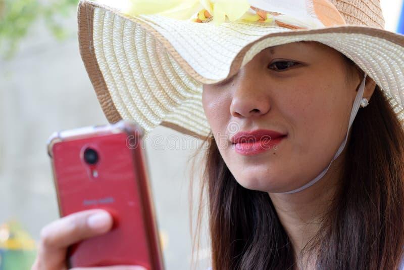 Cara bonita da mulher da Idade Média que veste o Internet da consultação do chapéu de domingo com sorriso esperto do telefone imagem de stock royalty free