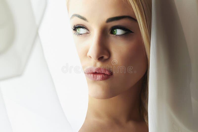 Cara bonita da mulher loura nova da noiva. Olhar da menina no véu de Window.Bridal. Cortinas fotos de stock royalty free