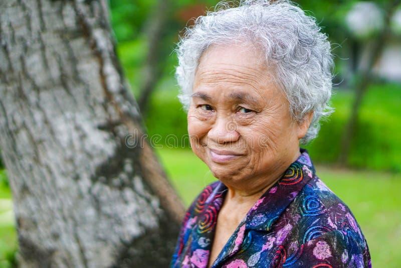 Cara brilhante asiática do sorriso superior ou idoso da mulher adulta com saúde forte ao andar no parque no feriado imagens de stock