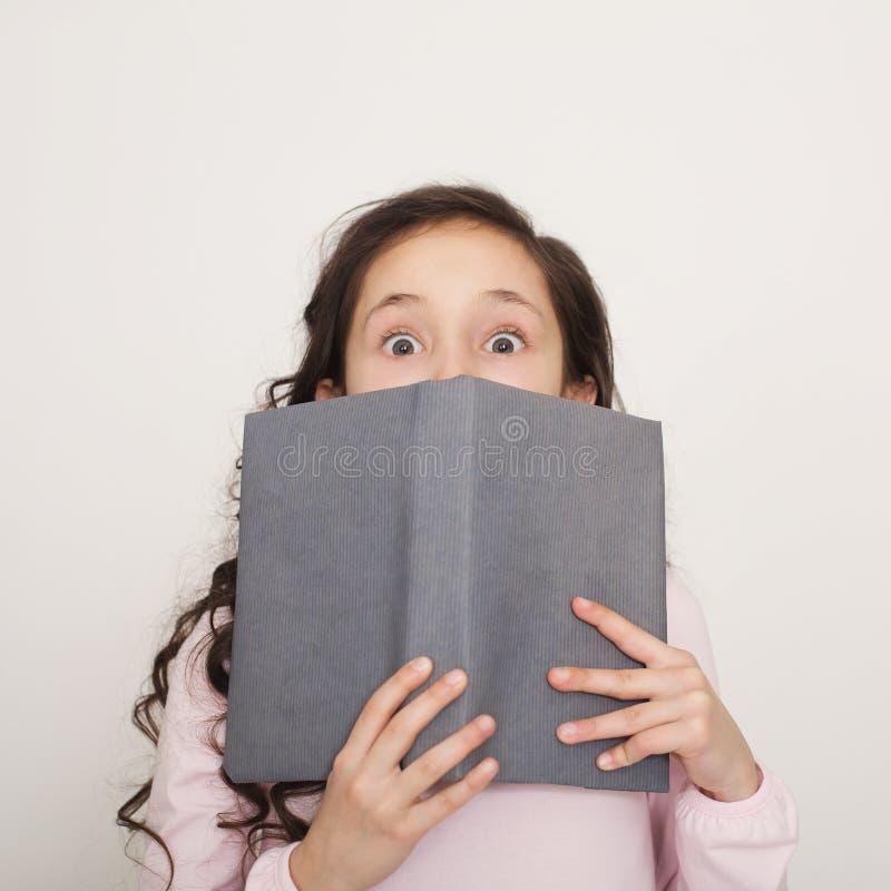 Cara chocada de la cubierta de la niña con el libro fotografía de archivo libre de regalías