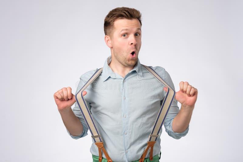 Cara chocada do homem europeu novo na camisa e em suspensórios azuis foto de stock