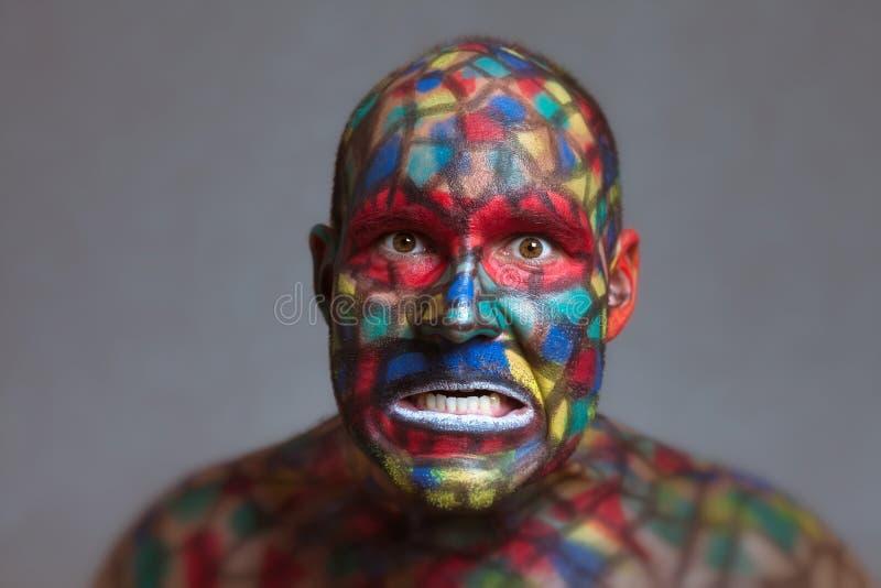 Cara colorida del malvado furioso que le mira fotos de archivo libres de regalías