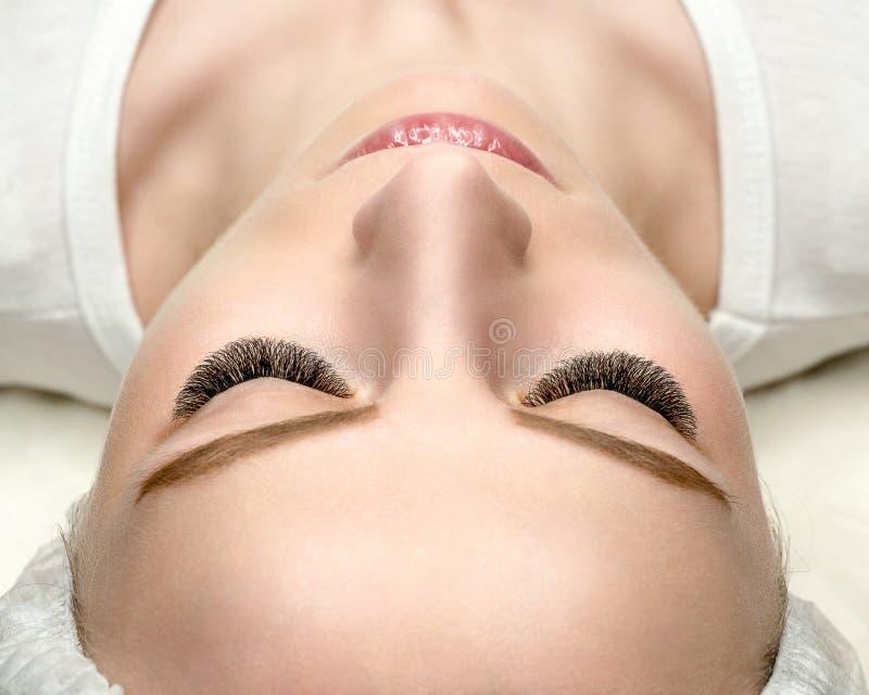 Cara con extensiones de la pestaña, piel bien para arriba preparada, visión superior, cierre de la mujer, foco selectivo foto de archivo libre de regalías