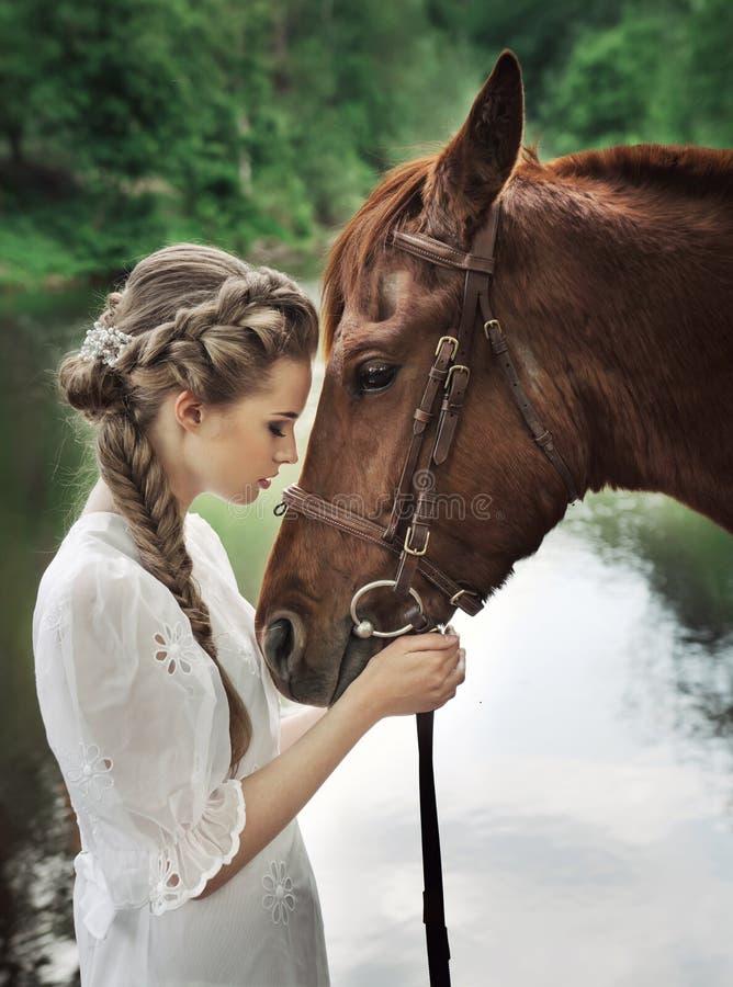 Cara conmovedora del caballo de la mujer foto de archivo libre de regalías