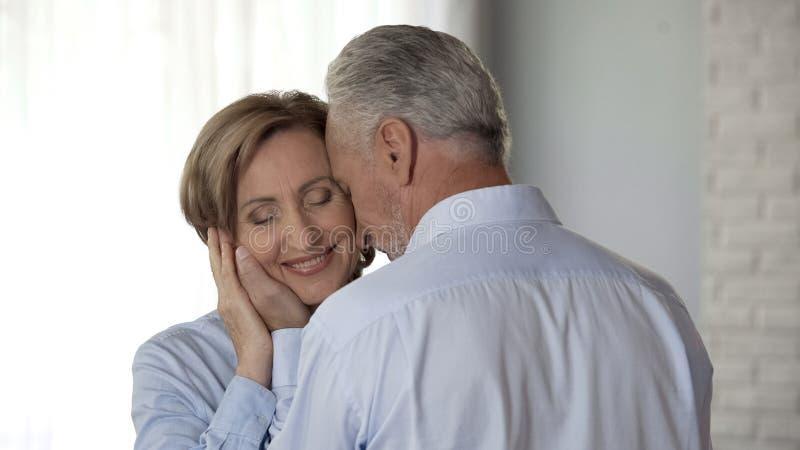 Cara conmovedora masculina envejecida de las señoras con el amor, armonía en matrimonio duradero imagenes de archivo