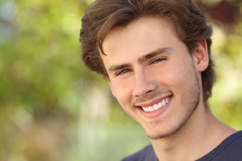 A cara considerável do homem com um branco aperfeiçoa o sorriso foto de stock