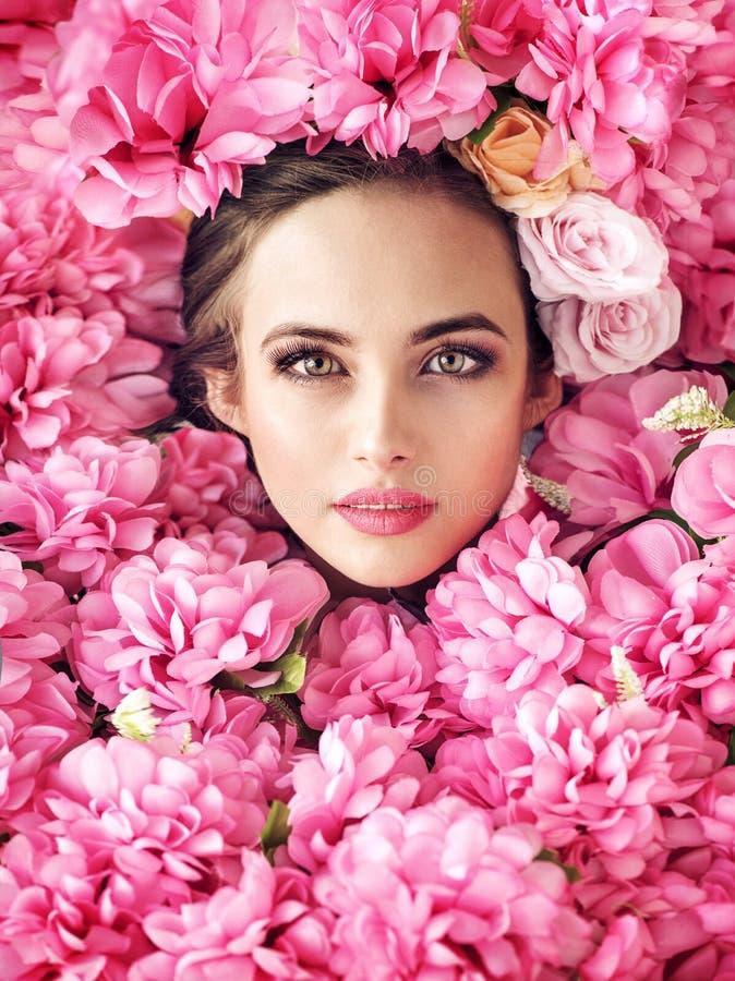 Cara consideravelmente fêmea entre flores cor-de-rosa imagem de stock