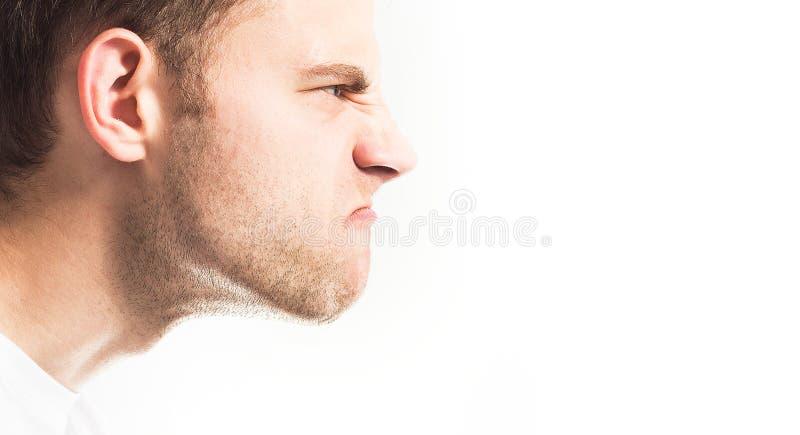 Cara contrariedad, enojada de un hombre en un fondo blanco en perfil fotografía de archivo libre de regalías