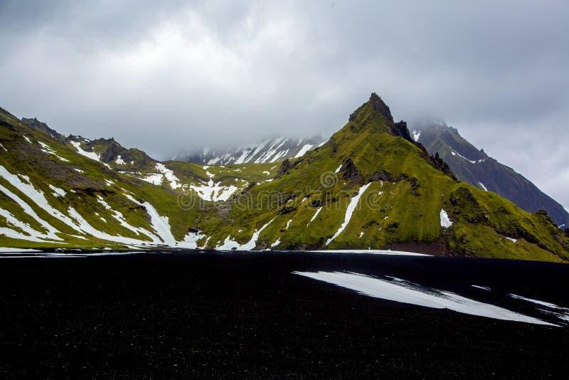 Cara cubierta verde de la roca con la arena de la ceniza negra imagen de archivo