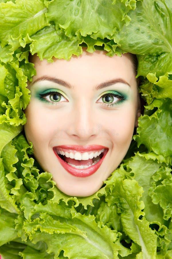 A cara da beleza da mulher com alface fresca verde sae fotografia de stock royalty free