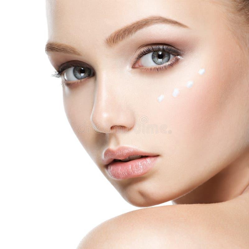 Cara da beleza da mulher com creme cosmético na cara imagens de stock