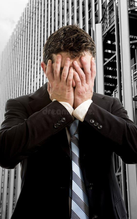Cara da coberta do homem de negócios desesperada na frente do distrito financeiro do prédio de escritórios foto de stock