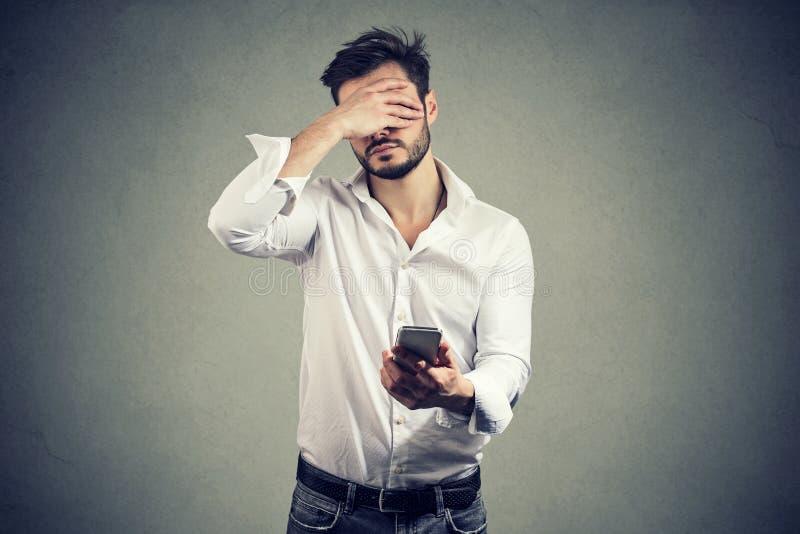Cara da coberta do homem no desespero que tem más notícias no smartphone contra o fundo cinzento fotografia de stock