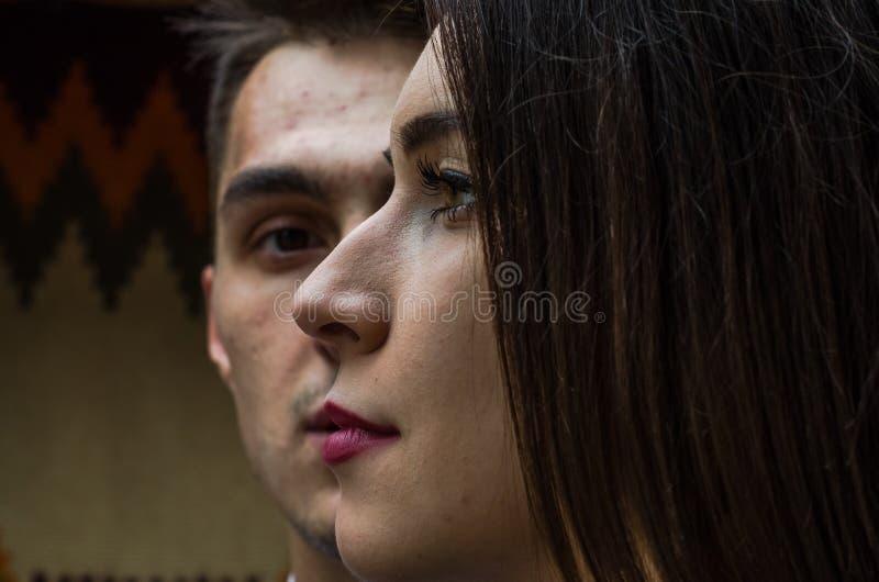 Cara da menina bonita nova que olha na distância na cara do fundo do indivíduo novo, um par no amor foto de stock