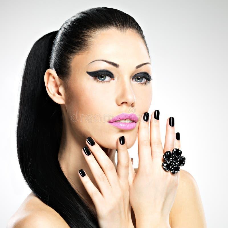 Cara da mulher bonita com pregos pretos e os bordos cor-de-rosa imagens de stock