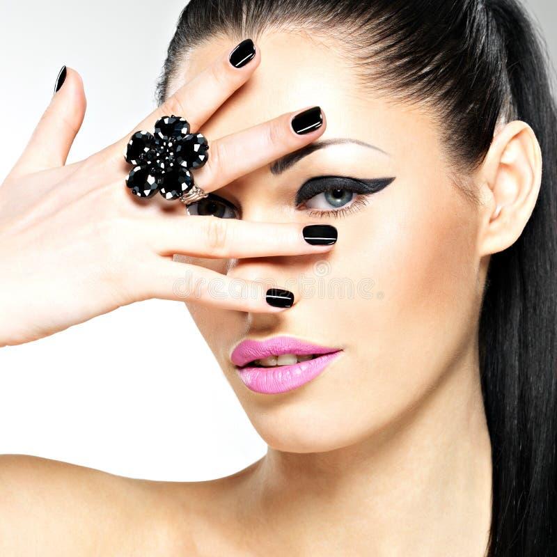 Cara da mulher bonita com pregos pretos e os bordos cor-de-rosa fotografia de stock royalty free
