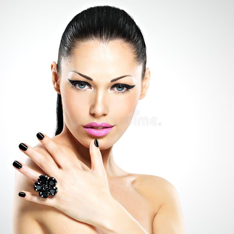 Cara da mulher bonita com pregos pretos e os bordos cor-de-rosa fotografia de stock