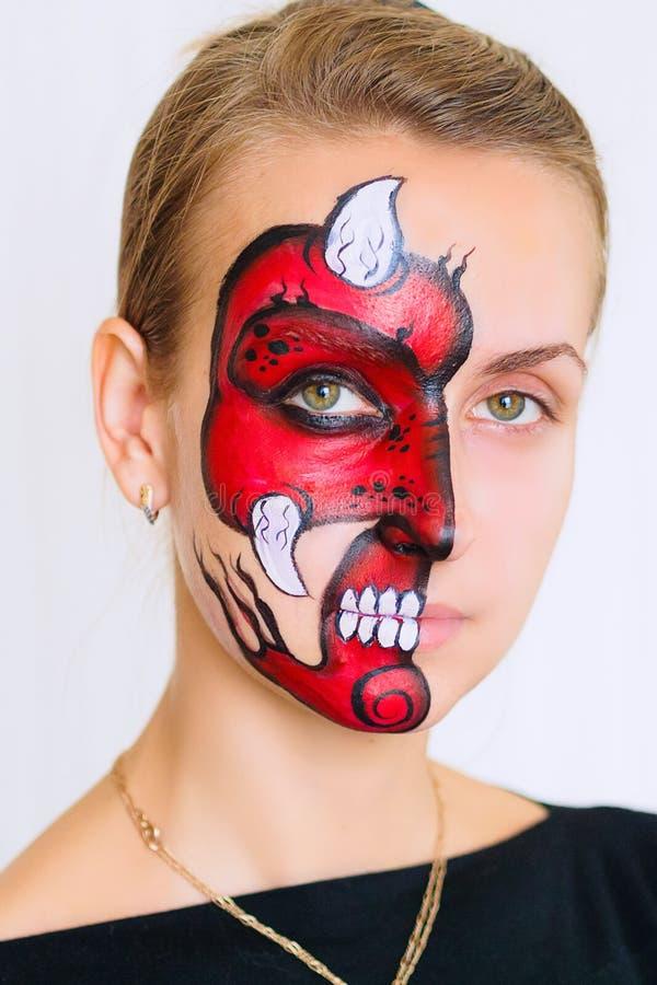 Cara da mulher com máscara pintada do diabo nela no fundo branco imagens de stock