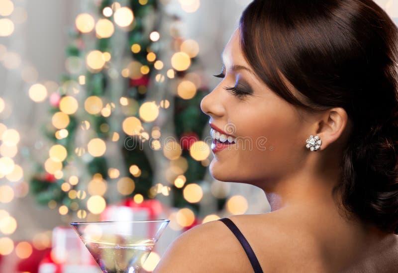 Cara da mulher com o cocktail sobre luzes de Natal fotos de stock