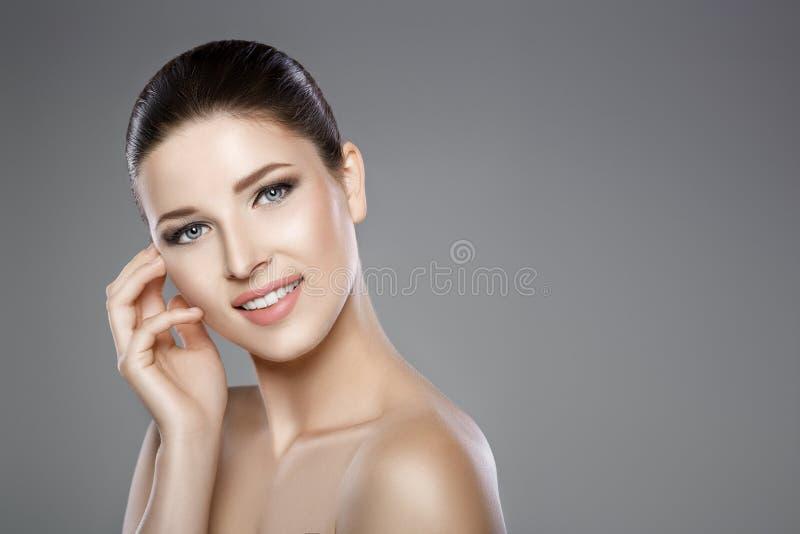 A cara da mulher com olhos azuis e limpa a pele fresca Sorriso bonito e dentes brancos fotografia de stock