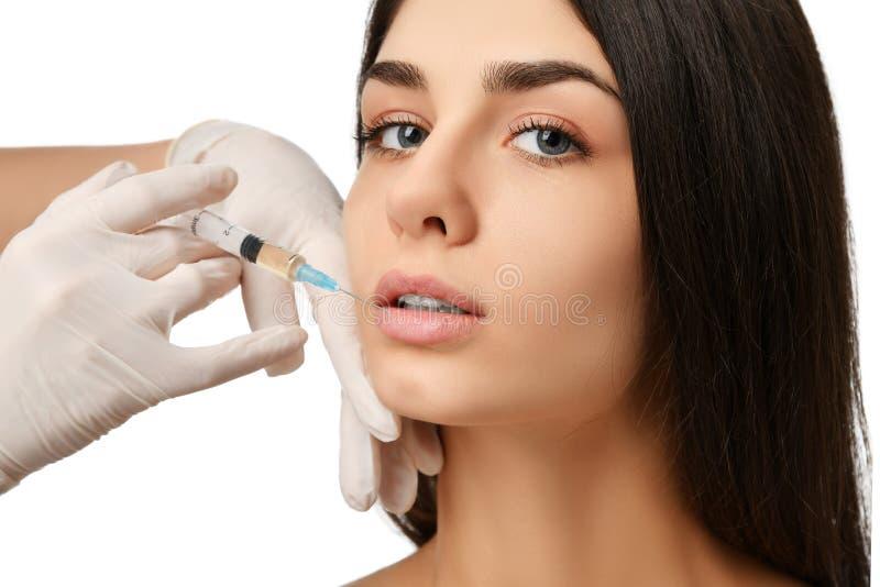 Cara da mulher do conceito plástico da beleza da cirurgia dos bordos e mão morenos novas do doutor na luva com seringa fotos de stock