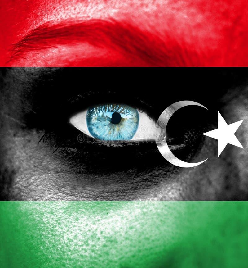 Cara da mulher pintada com a bandeira de Líbia foto de stock