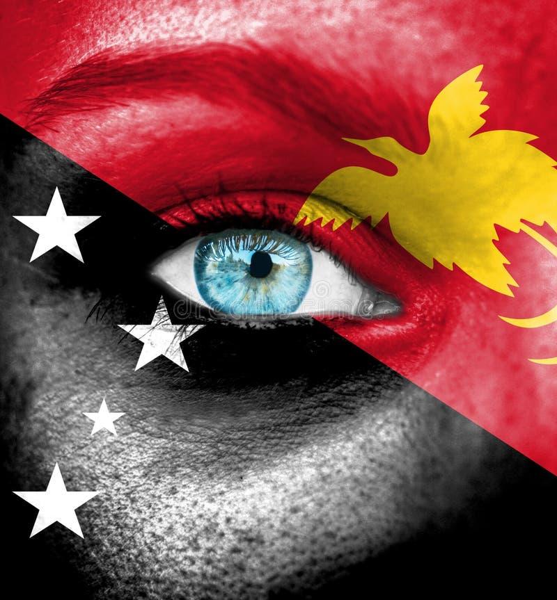 Cara da mulher pintada com a bandeira de Papua Gunea novo imagem de stock