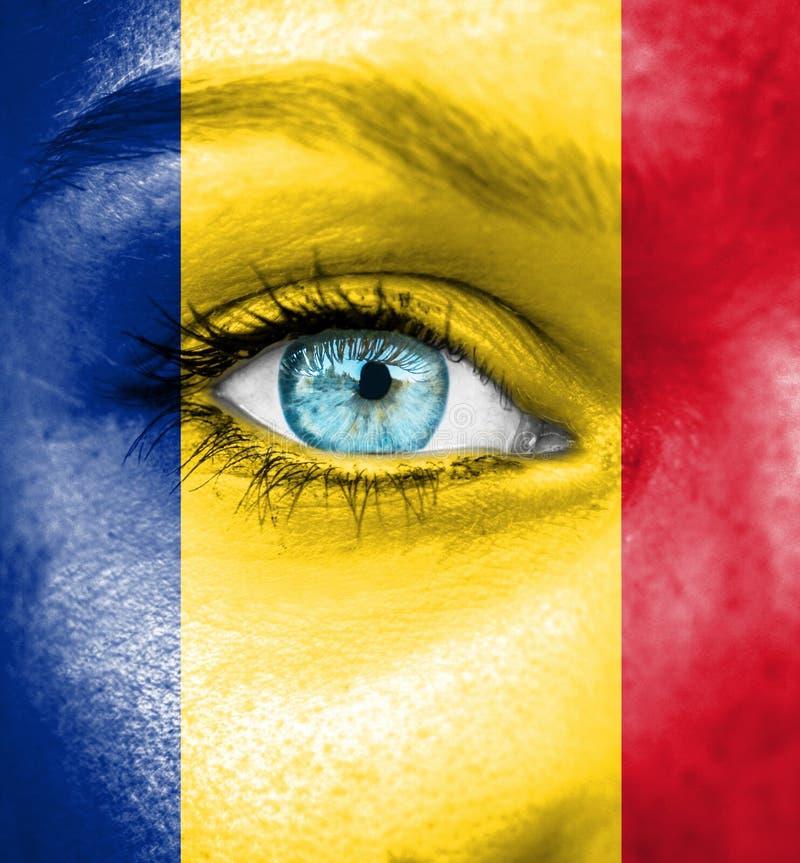 Cara da mulher pintada com a bandeira de Romênia imagem de stock royalty free