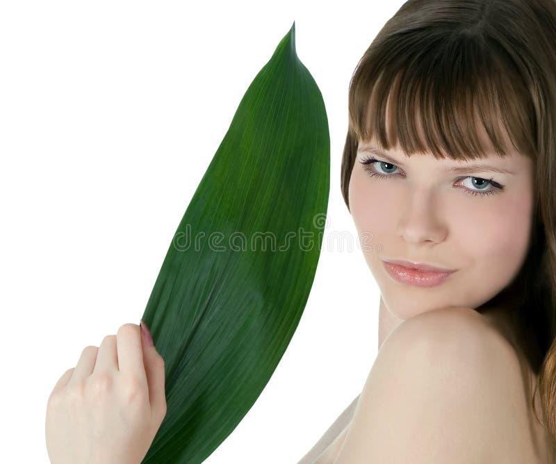 cara da mulher que esconde atrás da folha de palmeira verde grande fotografia de stock royalty free