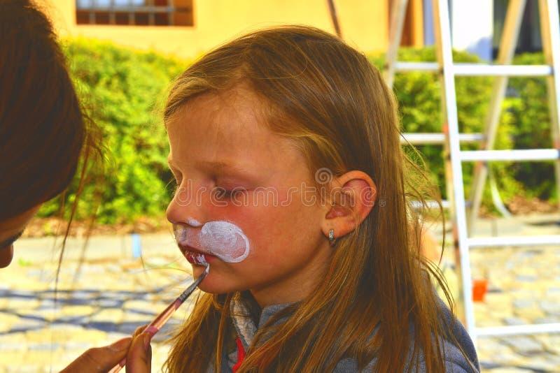 Cara da pintura da mulher da criança fora pintura da cara do bebê Menina que obtém sua cara pintada como um coelho por artis da p fotografia de stock