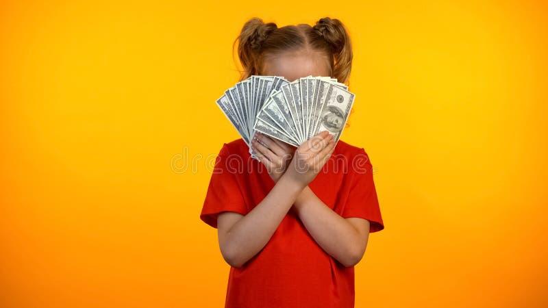 Cara de cierre del adolescente juguetón con los billetes de banco del dólar, felices con la primera renta fotos de archivo libres de regalías