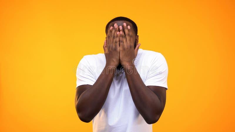 Cara de coberta masculina preta amedrontada pelas mãos, sentindo assustados, reação do esforço foto de stock royalty free